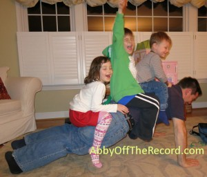 Superdad doing pushups with 3 kids on his back