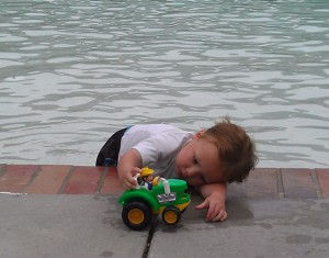 Toddler playing with a truck at the pool