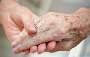 a young hand holding an older person's hand