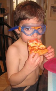 Miles eating pizza with goggles on