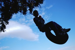 Silhouette of Boy Swinging on a Tire