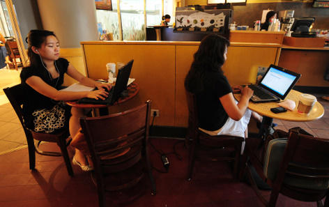 Women use their laptop computers at a coffee shop