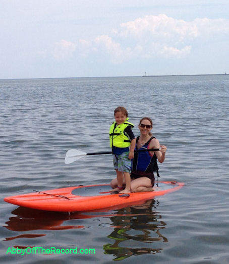 Me, stand-up paddle boarding with my 4yo son