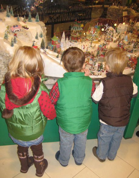 kids looking at a holiday train garden