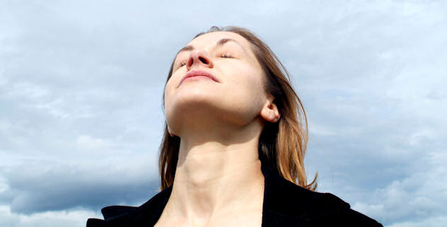 Woman taking a deep breath outside