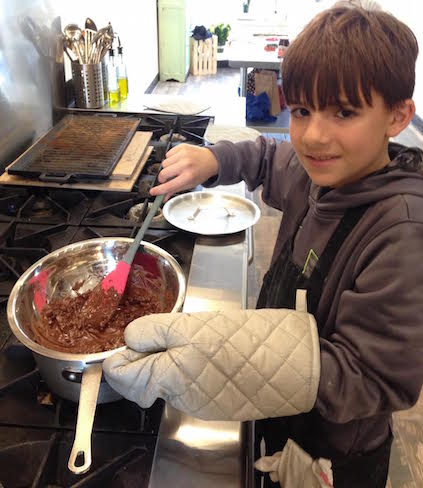 Kid chef learning to melt chocolate