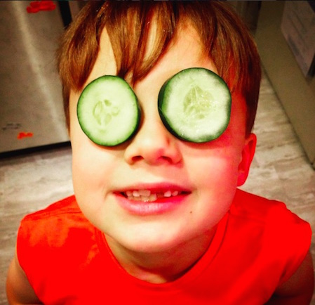 My son with cucumber slices over his eyes